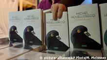 The new book of French novelist and poet Michel Houellebecq is presented at a reading in Cologne, Germany, Monday, Jan. 19, 2015. The controversial author appears in public for the first time after his book Soumission (submission) was published on the day of the Charlie Hebdo shooting in Paris. A cartoon of Houellebecq was published on the magazine's cover page that day, giving attention to his book, describing a future France where a Muslim president is ruling the country according to Islamic law. (AP Photo/Martin Meissner)