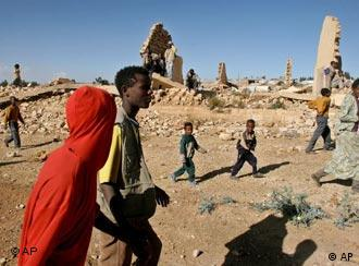 People walk past destroyed houses in what used to be a city center in Ethiopia