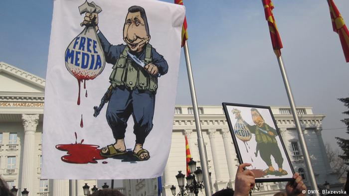Against the backdrop of Macedonia's parliament, a cartoon depicting Macedonian Prime Minister Nikola Gruevski can be seen. In it, he is holding up a sack captioned Free Media; blood is dripping from the sack and in Gruevski's other hand, he holds a bloody knife. Journalists in Skopje were staging a protest against the imprisonment of Macedonian reports, in January 2015. (Photo: DW/Katerina Blazevska)