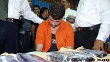 TANGERANG, INDONESIA: Brazilian Rodrigo Gularte (C) is presented to the media along with seized six kilograms (13.2 pounds) of cocaine at the Customs office of Sukarno-Hatta airport in Tangerang, 05 August 2004. Gularte was arrested 31 July for attempting to smuggle a large quantity of cocaine into Indonesia hidden inside a surfboard. AFP PHOTO (Photo credit should read STR/AFP/Getty Images)