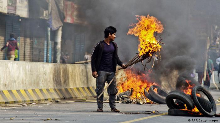 Bangladesh Nationalist Party (BNP) supporters set fire to tyres and material in the street during a clash with police outside a court in Dhaka on December 24, 2014, during a court appearance by party chief Khaleda Zia (Photo: STRDEL/AFP/Getty Images)