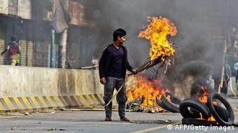 Bangladesh Nationalist Party (BNP) supporters set fire to tyres and material in the street during a clash with police outside a court in Dhaka on December 24, 2014 STRDEL/AFP/Getty Images