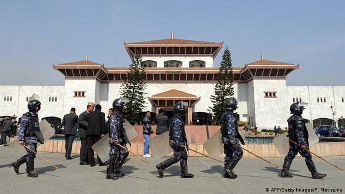 Nepalese police in riot gear walk past the parliament building in Kathmandu on January 22, 2015 (Photo: PRAKASH MATHEMA/AFP/Getty Images)