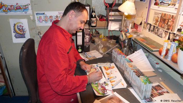 Karneval Wagenbauer Jacques Tilly sitzt am Schreibtisch und zeichnet
