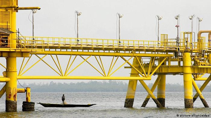 A Nigerian in a wooden canoe paddles under a yellow oil rig