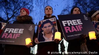 Protesters are holding candles and signs that say Free Raif. (Photo: Anthony Devlin/PA Wire)