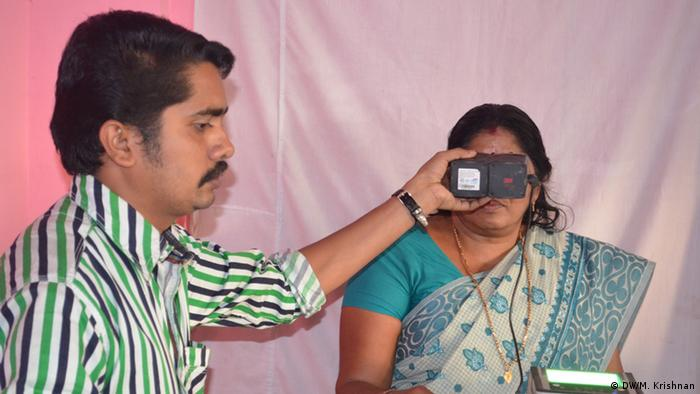 An Indian woman's eyes are scanned as identification for a government identity card