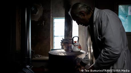 A doctor heats a stove upon which a kettle sits