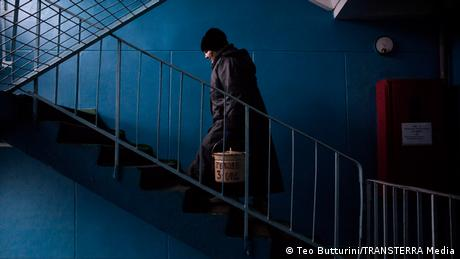 A patient carries food in a pail from the kitchen up a staircase