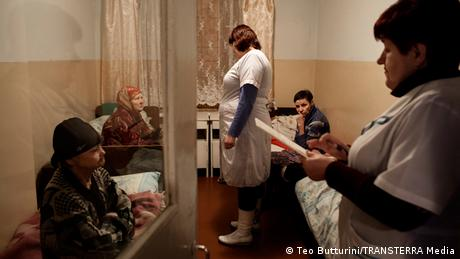 A doctor and nurse talk to patients crowded into a room with beds