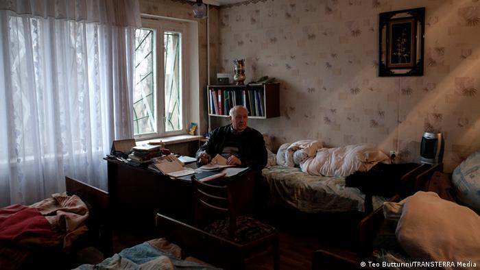 Лікар за своїм робочим столом в оточенні ліжок