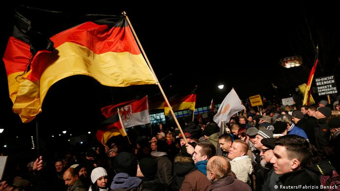 Protesters wave a flag at a PEGIDA march in Dresden