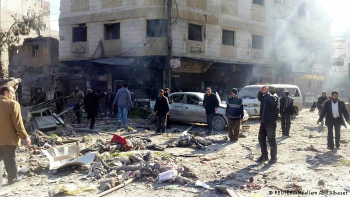 Residents react to dead bodies in town square after shelling by forces loyal to Syria's President Bashar al-Assad
