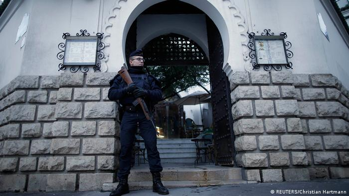 A French police officer stands guard in front of the entrance of the Paris Grand Mosque