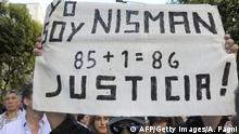 A man holds a placard that reads I am Nisman, 85+1, Justice during a rally in front of the headquarters of the AMIA (Argentine Israelite Mutual Association), in Buenos Aires on January 21, 2015, to protest against the death of Argentine public prosecutor Alberto Nisman, who was found shot dead earlier, just days after accusing President Cristina Kirchner of obstructing a probe into a 1994 Jewish center bombing that killed 85 peiople and injured another 300. Nisman, 51, who was just hours away from testifying at a congressional hearing, was found dead overnight in his apartment in the trendy Puerto Madero neighbourhood of the capital. I can confirm that a 22-caliber handgun was found beside the body, prosecutor Viviana Fein said. The nation's top security official said Nisman appears to have committed suicide. AFP PHOTO/ALEJANDRO PAGNI (Photo credit should read ALEJANDRO PAGNI/AFP/Getty Images)