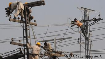 Pakistani technicians work on high voltage power lines in Lahore on January 13, 2011 (Photo: Arif Ali/AFP/Getty Images)