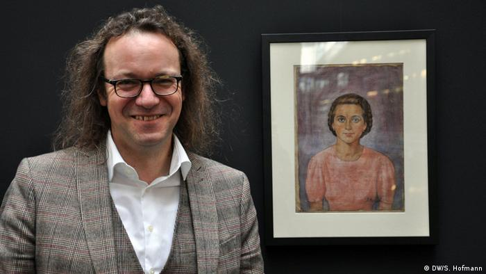 Jürgen Kaumkötter with a painting created in Auschwitz by Jan Markiel depicting the daughter of the camp baker, Copyright: DW/S. Hofmann