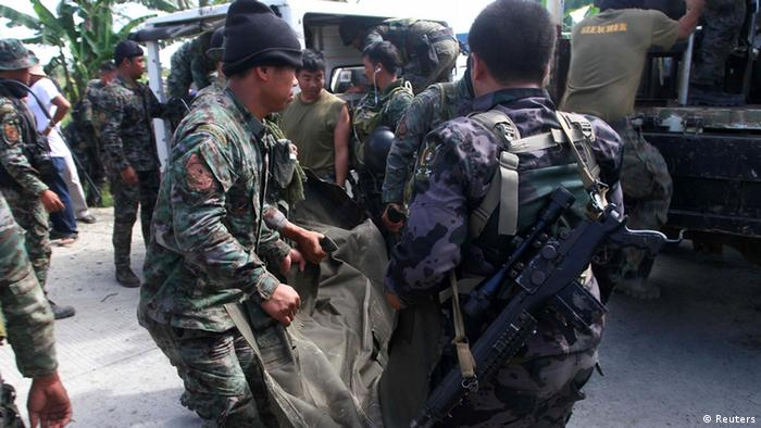 Philippine National Police (PNP) carry a body bag, containing a member of the Special Action Force, to a van in Mamasapano town, Maguindanao province, January 26, 2015 (Photo: REUTERS/Stringer)