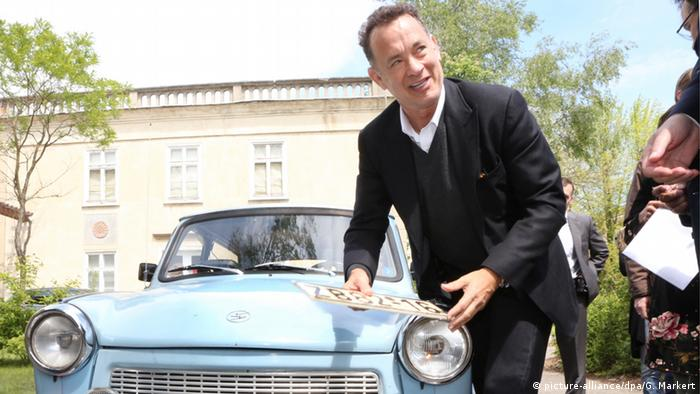 Tom Hanks in Eisenhüttenstadt in 2014, holding the license plate in front of the sky-blue Trabi.