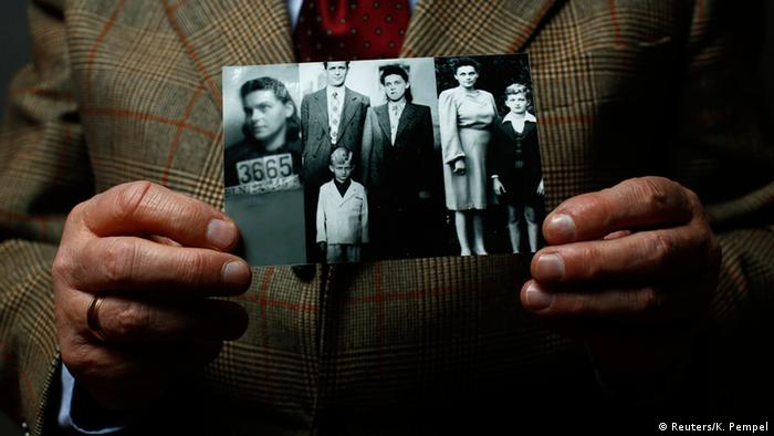 Auschwitz death camp survivor Jacek Nadolny, 77, who was registered with camp number 192685, holds up a wartime photo of his family, Copyright: REUTERS/Kacper Pempel