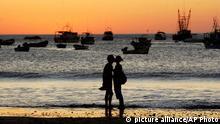 Tourists kiss as the sun sets on the beach of San Juan del Sur, 141km (88 miles) south of Managua, Nicaragua, late Thursday, Feb. 17, 2005. (AP Photo/Esteban Felix) **EFE OUT**
