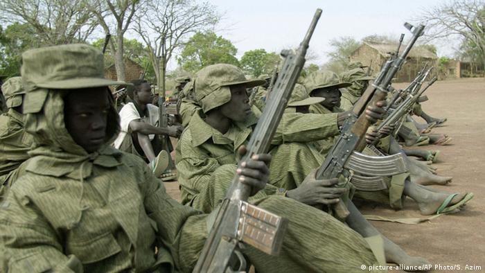 Sudenasische Kindersoldaten sitzen nebeneinander und halten ihr Maschinengewehr in der Hand. (Foto: picture-alliance/AP Photo/S. Azim)