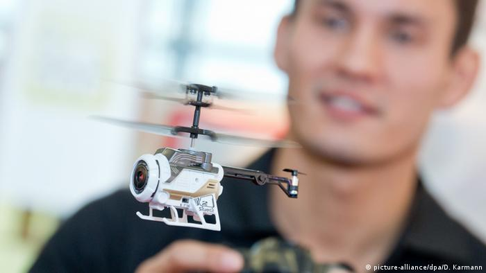 An adult flies a remote-controlled helicopter