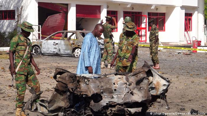 Nigerian soldiers look over a shell of car blasted by a suicide bomber.