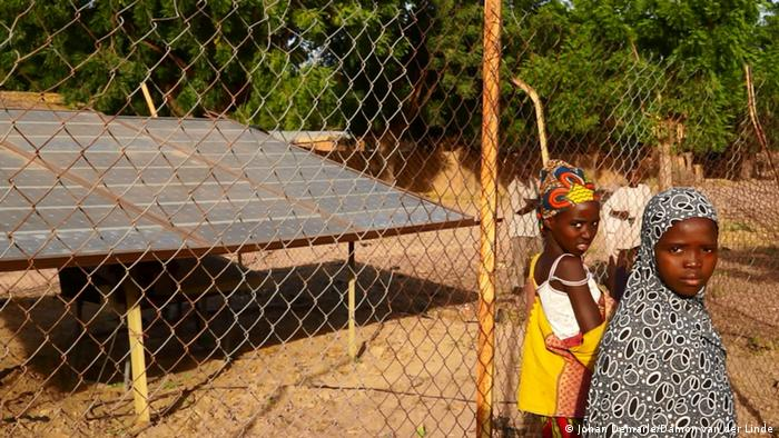 Children walk past a solar panel in northern Nigeria.