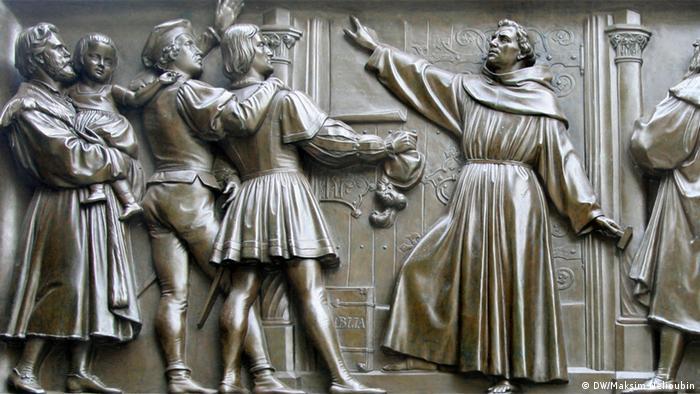 Лютер вывешивает 95 тезисов на дверях Замковой церкви в Виттенберге. Один из барельефов монумента в Вормсе