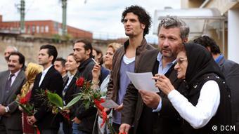 Mehrere Männer mit Blumen und ein paar alte Frauen stehen Spalier © DCM