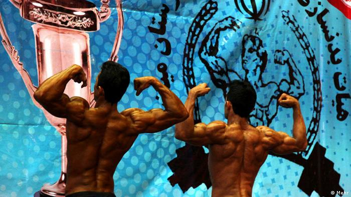 Photo: two posing bodybuilders from the back