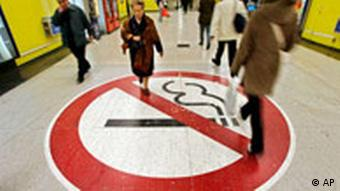 Passengers in the Madrid metro walk over a giant no-smoking sign