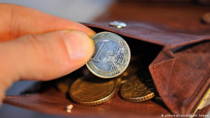 A hand takes out a euro coin from a wallet