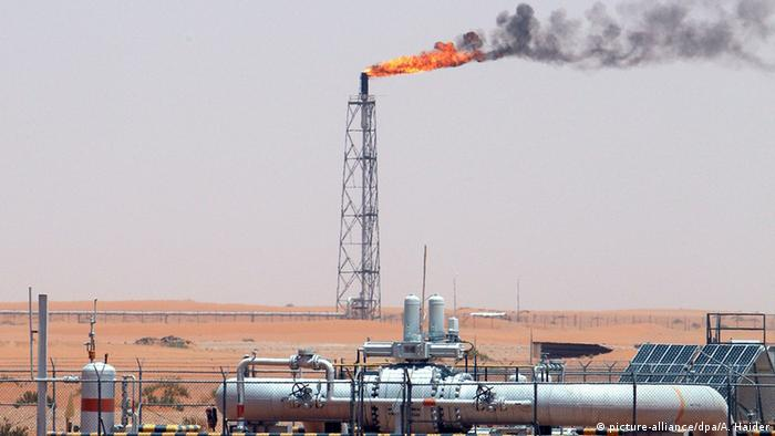 Oil field in Saudi Arabia with equipment in foreground and tower with flame on top in the background (picture-alliance/dpa/A. Haider)