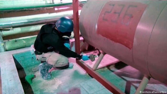 A foreign worker examining chemical weapons in Syria, 2013
