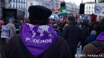 A protester wears a scarf that says 'Podemos'