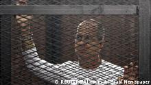 Al Jazeera journalist Peter Greste of Australia stands in a metal cage during his trial in a court in Cairo in this March 24, 2014 file photo. Greste, imprisoned in Egypt 400 days ago on charges that included aiding a terrorist group, will be deported to his native Australia on February 1, 2015, Egypt's state news agency reported. REUTERS/Al Youm Al Saabi Newspaper/Files (EGYPT - Tags: POLITICS CRIME LAW MEDIA) EGYPT OUT. NO COMMERCIAL OR EDITORIAL SALES IN EGYPT