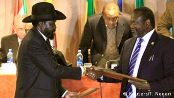 President Salva Kiir and rebel leader Riek Machar exchange documents after signing a ceasefire in February 2015