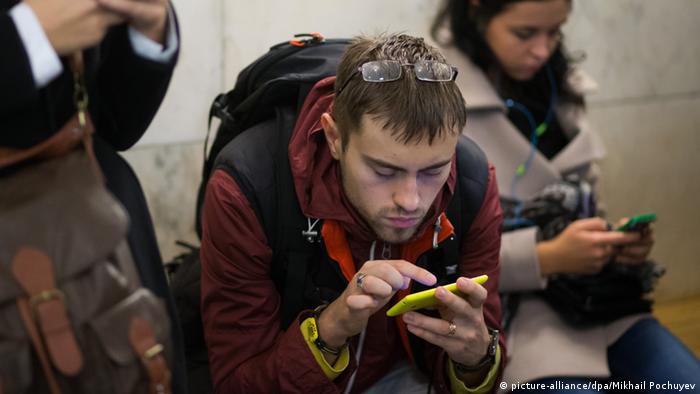 Молодые люди со смартфонами в вагоне московского метро
