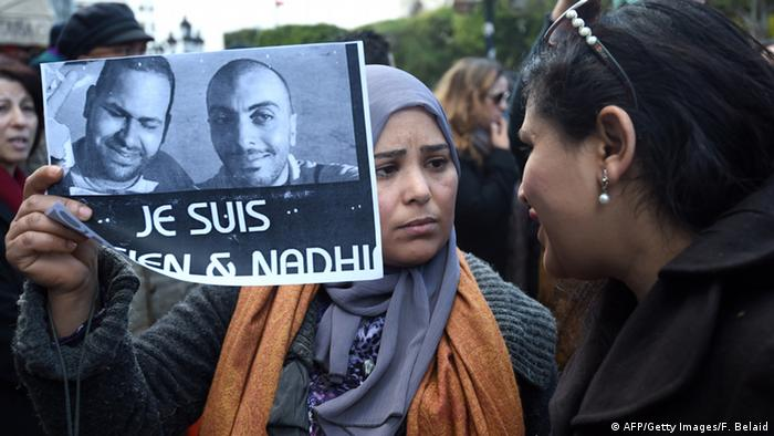 A Tunisian demonstrator holds a placard with the photo of Tunisian journalists Sofiene Chourabi and Nadhir Ktari (photo: FETHI BELAID/AFP/Getty Images)