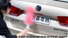 ARCHIV - HANDOUT - Eine Frau säubert am 20.04.2013 auf dem VW-Messestand auf der Auto Shanghai im chinesischen Shanghai das Heck eines Volkswagen Santana. Foto: Friso Gentsch/Volkswagen/dpa (zu dpa: Chinas Kampagne gegen Korruption erreicht Volkswagen vom 27.08.2014) +++(c) dpa - Bildfunk+++