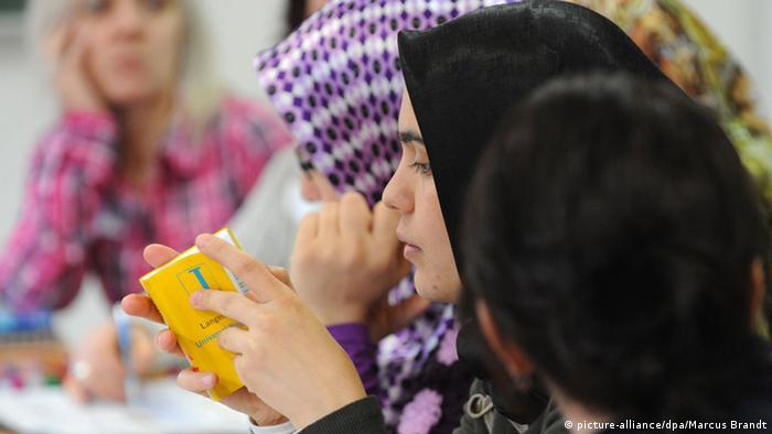 Deutschkurs-Teilnehmerin blättert in einem Wörterbuch (Foto: dpa)