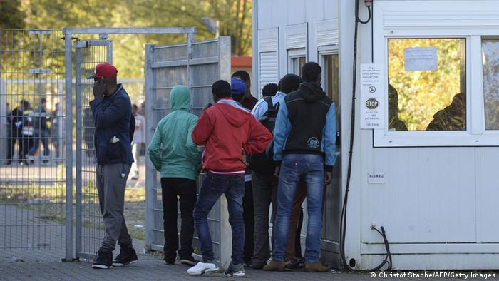 Refugees wait at entrance to housing