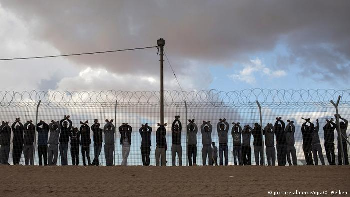 Protesting African migrants stand holding their arms aloft at the Holot detention center