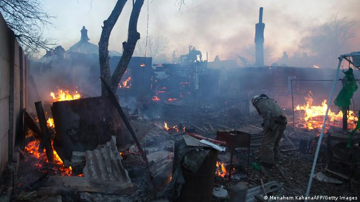 Firefighters tackle a blaze after shelling destroyed several houses near the airport in Donetsk