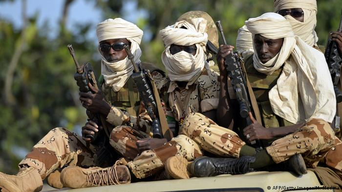 Chadian soldiers in military attire and carrying automatic weapons sit on top of a pickup truck.