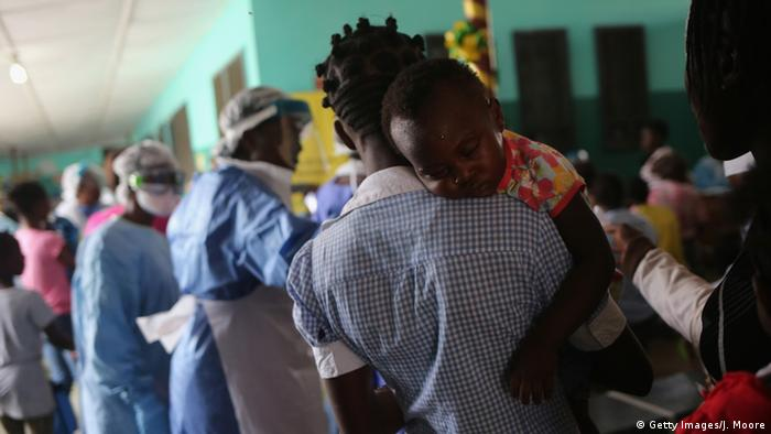 A woman carries her baby inside a hospital in Liberia (Getty Images/J. Moore)