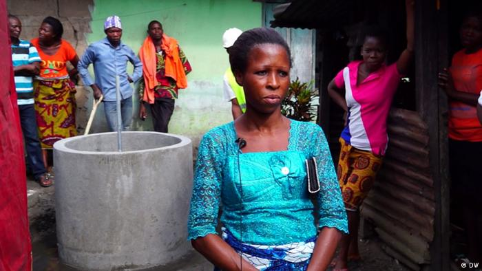 A woman sitting next to a grey container that converts kitchen waste into fuel