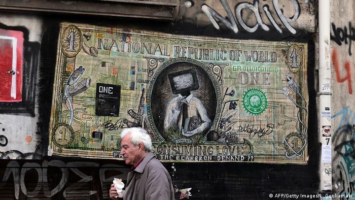 A man walks past a graffiti criticizing predatory lending practices in Athens, Greece